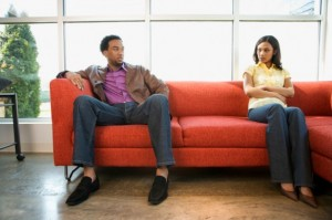 when sorry isn't enough. couple sitting on couch talking.